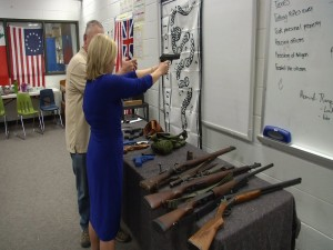 Reporter Lena Howland of KRDO handles guns in a Colorado City middle school.