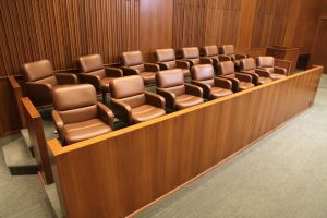 Invisible jury prepares to hear case against unknown person for unspecified damages.