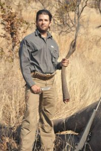 Donald Trump, Jr. holding an elephant's tail.
